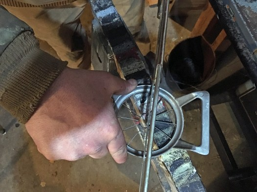 Apple corer balanced on a  sawhorse as a man cuts a small notch into the top of the apple corer