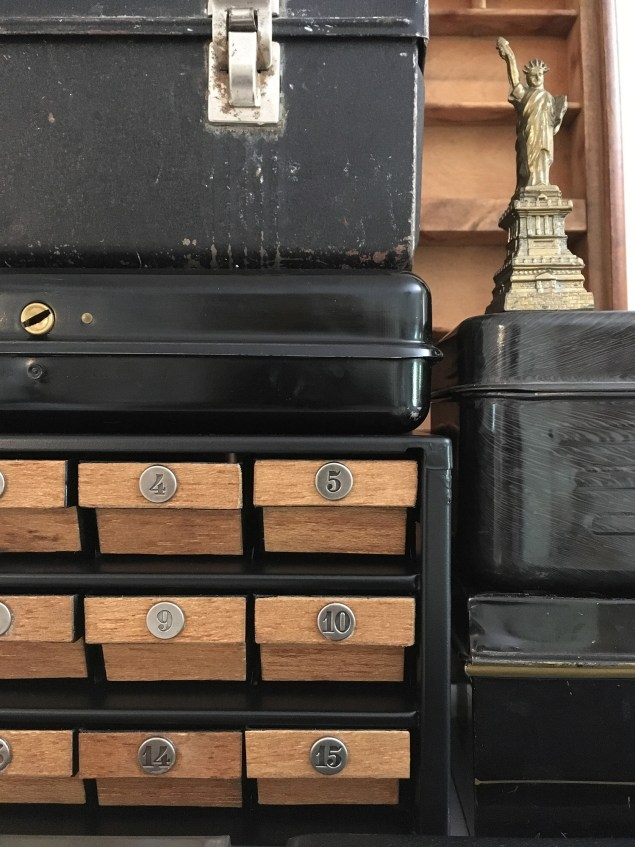 Black metal hardware organizer with wood drawer fronts