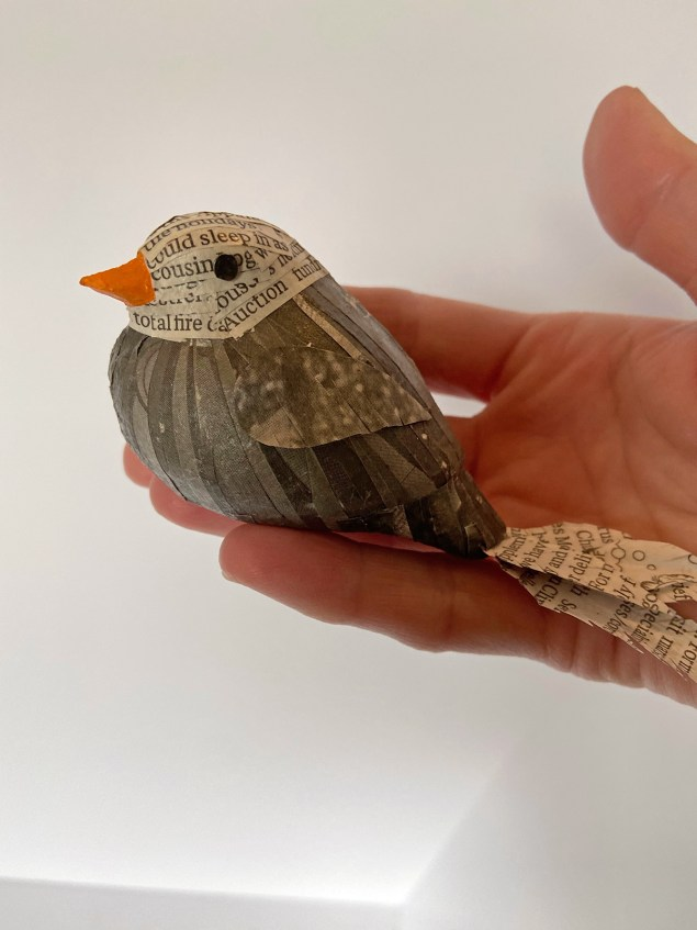 woman's hand holding newspaper bird
