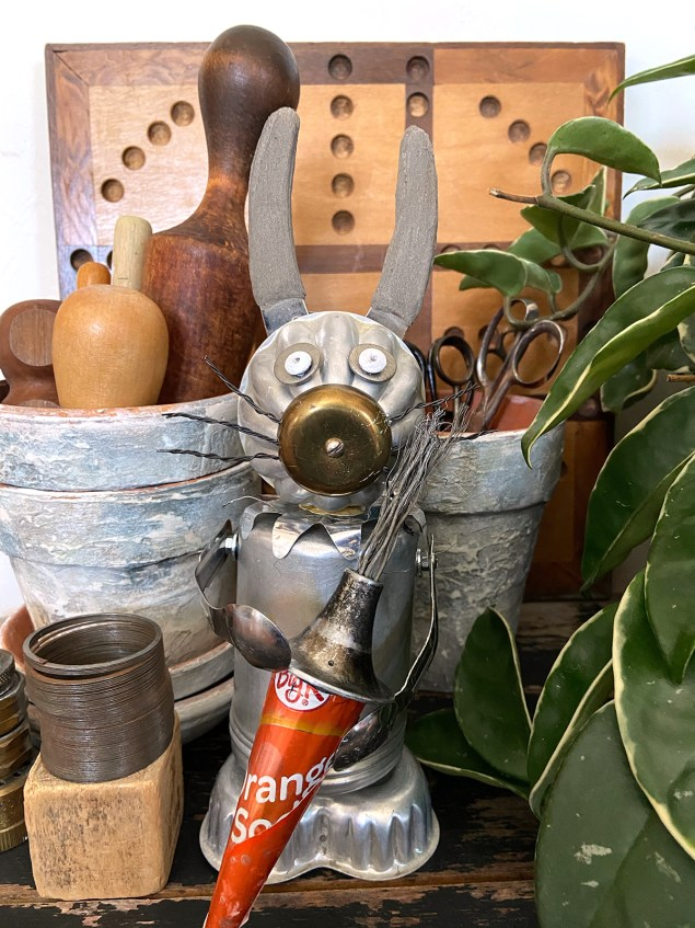 junk rabbit on table with flower pots, knick knacks, and a green plant