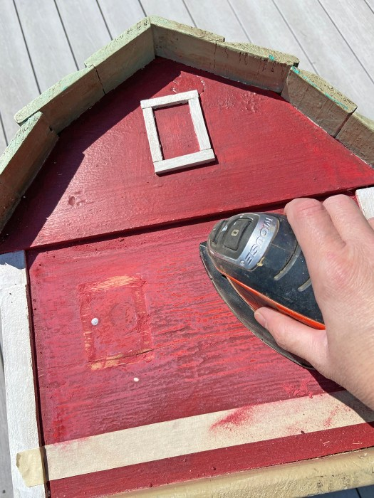 a woman's hand holding a Mouse sander over the end of a wooden toy barn