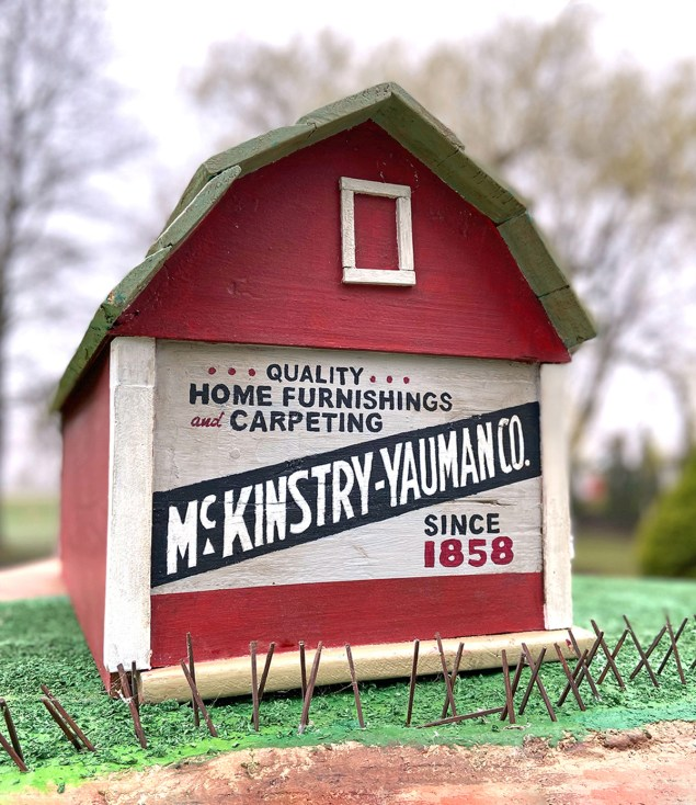 miniature wooden barn with a vintage advertising mural for McKinstry-Yauman Co. painted on it