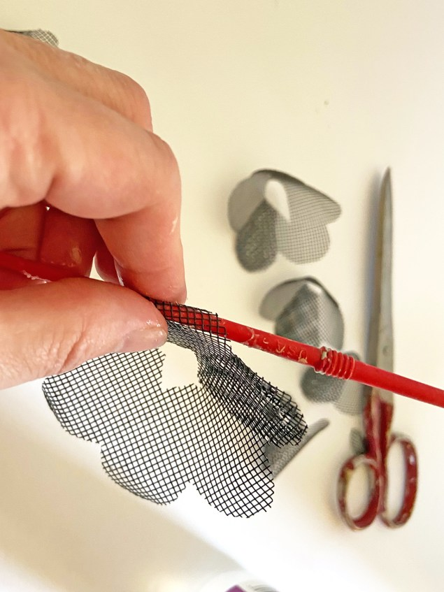 woman's hand rolling a black mesh flower petal around the barrel of a small paintbrush