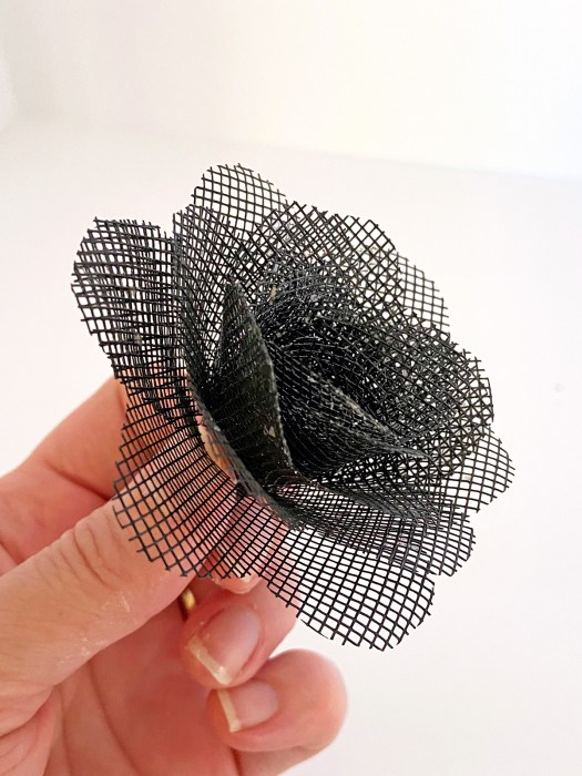 woman's hand displaying a full-sized black mesh flower that will become part of a bouquet of window screen roses