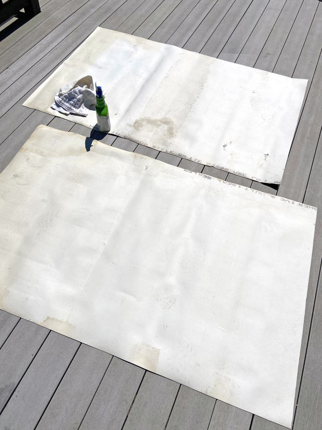the back of two pieces of vinyl flooring with a spray bottle of cleaning product resting on one of them