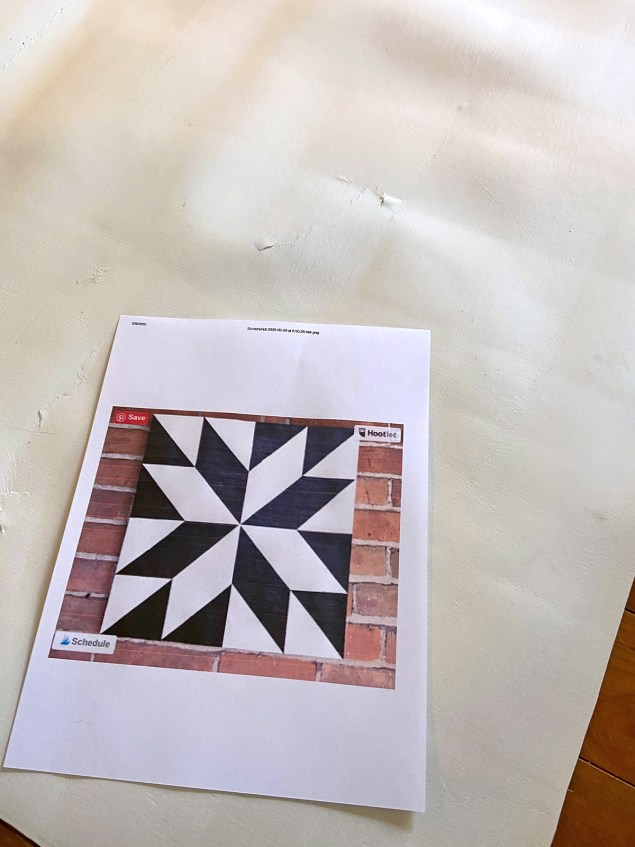 Vinyl flooring with a printout of a black and white barn quilt laying on top of it