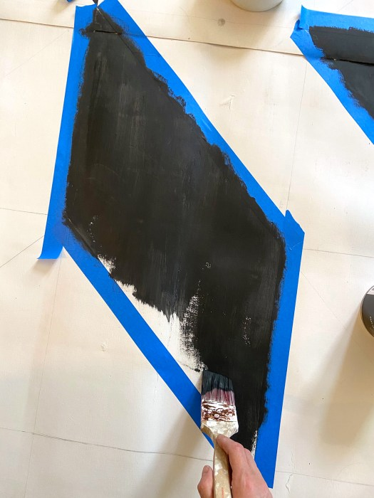 Closeup of one section of the vinyl flooring with a woman's hand holding a paintbrush over it and painting the section black