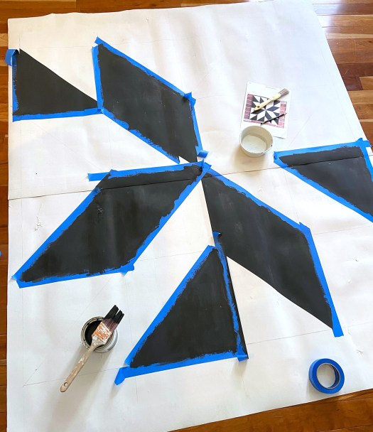 Barn quilt patio rug with six different shapes taped off in blue painters tape and the shapes filled in with black paint