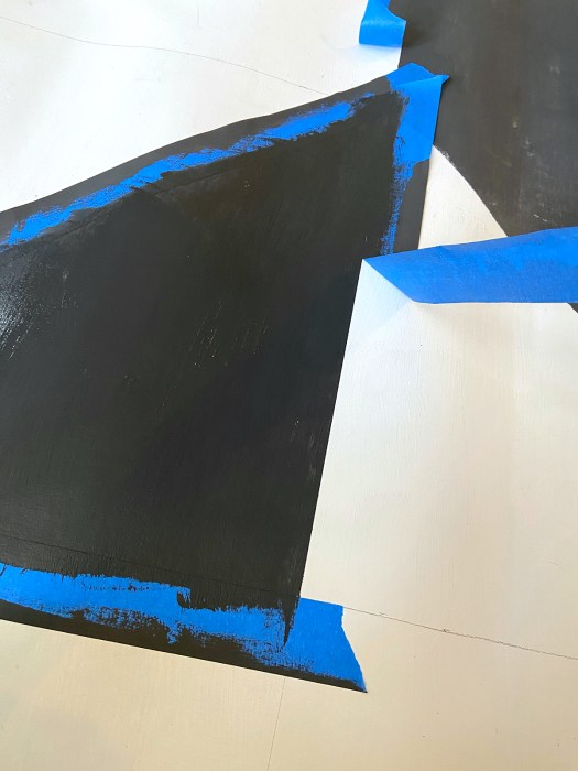 blue painters tape being peeled up off of a section of the vinyl flooring that was painted black