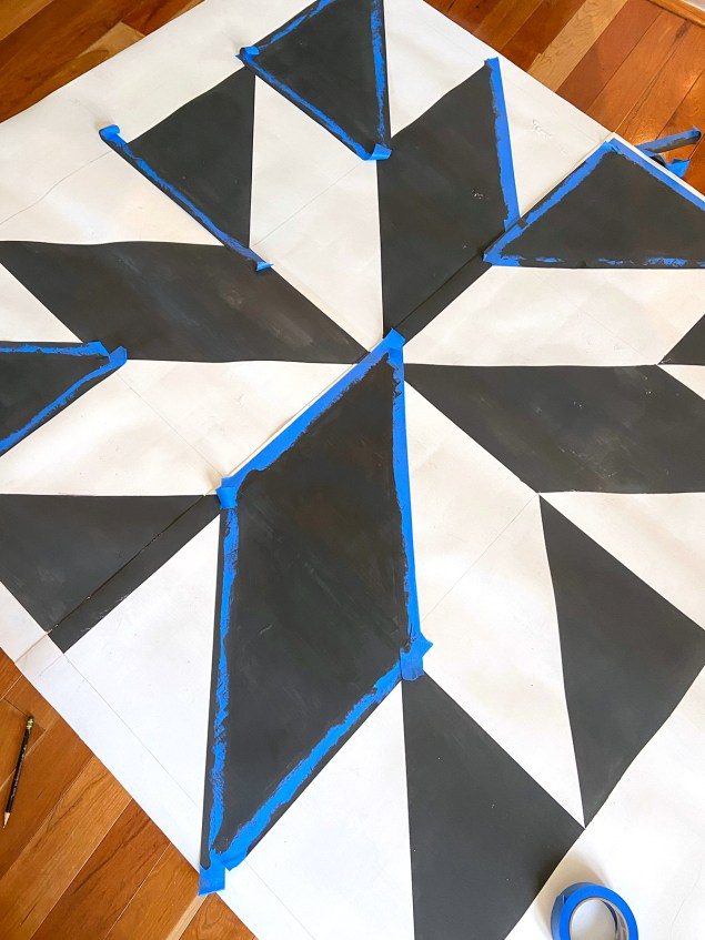 Barn quilt patio rug with all of the black sections painted on it and some of the blue painters tape still remaining