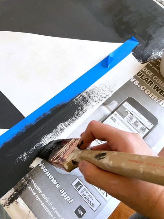 the edge of the vinyl with blue tape marking the border's edge and a woman's hand holding a paintbrush and painting the border black