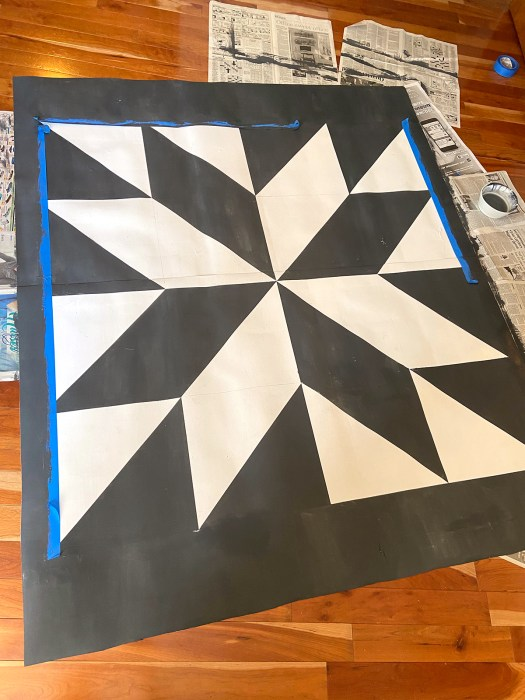 barn quilt patio rug with black border surrounding it