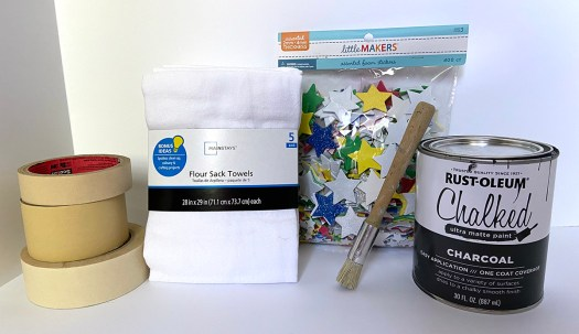 supplies for chalk painting on fabric: masking tape, flour sack dishtowels, adhesive stars, paint brush and can of Rust-Oleum Chalked paint in Charcoal