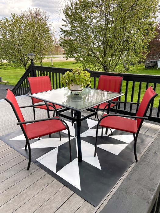 barn quilt patio rug with patio table and chairs sitting on it