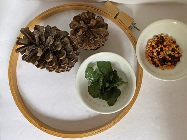 DIY embroidery hoop wreath materials: large embroidery hoop, pinecones, faux leaves and wooden beads