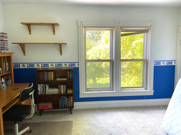 boys bedroom with blue and white walls, a desk and a book shelf, prior to a guest room/office makeover