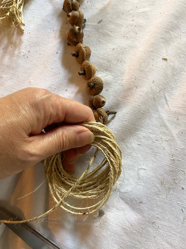 feeding the tail of the acorn garland through the loops of the tassel