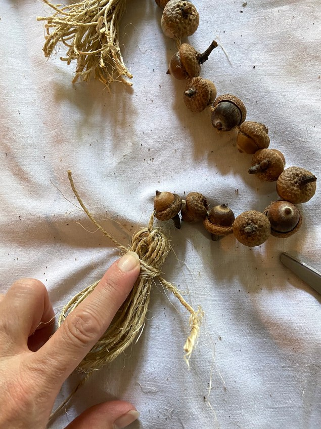 winding a piece of twine around the tassel about an inch from the top