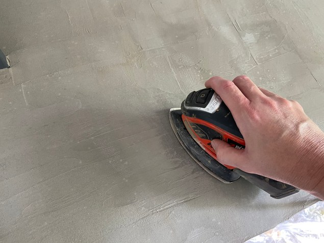 sanding off the high spots and ridges on the concrete desktop