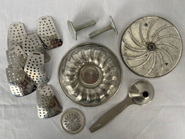 parts for a junk turkey assemblage: vegetable steamer flaps, mini Jell-O mold, leveling feet, cookie press disc, food processor blade and small funnel with handle