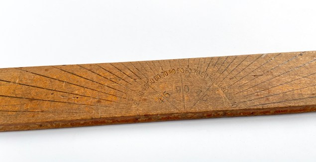 back of wooden ruler with compass angles printed on it