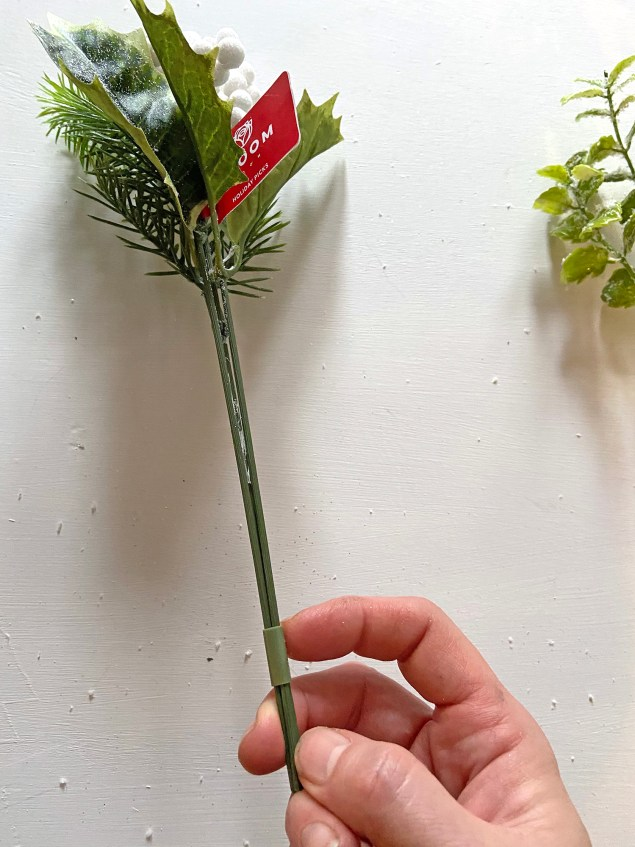 holly and berry picks attached at the stem by a green plastic band
