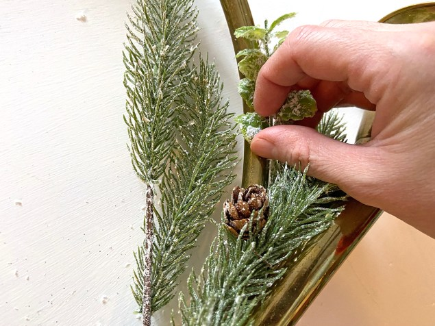 adding frosted eucalyptus to the French horn wreath
