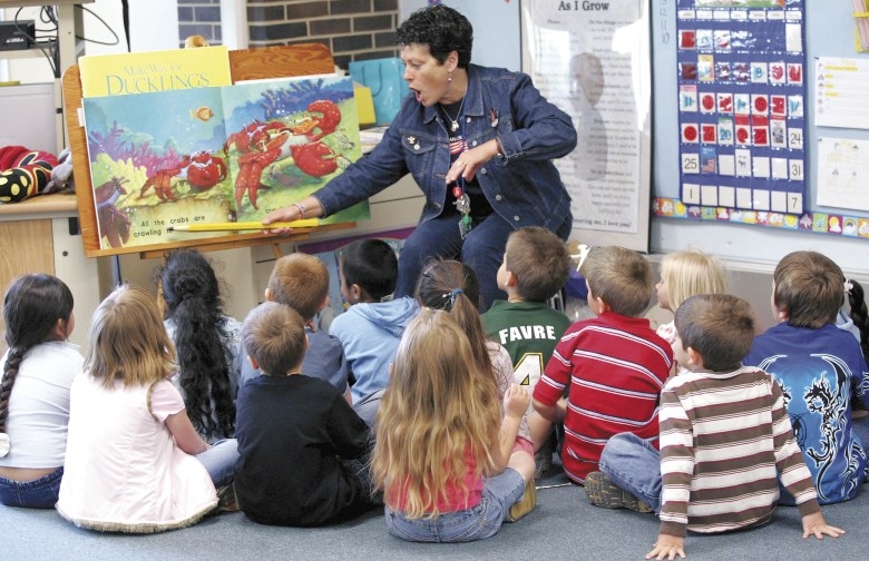 """Madison Elementary kindergarten teacher Kathie Koebler reads the book """"Splash in the Ocean"""" to her Janesville School District students in May. Some of the students have never had a book read to them before they got to the school. Photo Courtesy of THE JANESVILLE GAZETTE"""