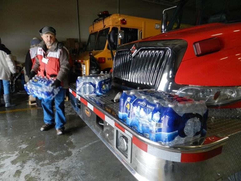 An American Red Cross volunteer stacks cases of bottled water at a Flint, Michigan, fire station in January. A state of emergency has been declared over the levels of lead in Flint's drinking water. Authorities also are providing free water filters to residents of the beleaguered city.