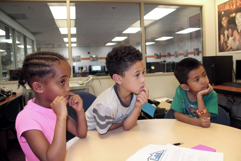 Left to right, Senyi Berisa, Damare McCollum and Idin Leuaxay sit attentively in Jacki Thomas' office at the Packer Townhouses community learning center in Madison.