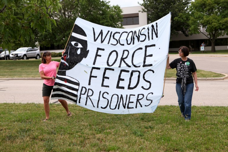 Wendy Turk, left, and Mary Jo Fesenmaier hold a banner decrying the force feeding of Wisconsin prisoners during a rally outside the state Department of Corrections headquarters in Madison, Wis. on July 5, 2016. Hunger striking prisoners and their advocates are seeking an end to long-term solitary confinement.