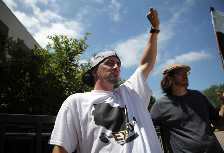 """Alan Schultz raises his fist as the Forward! Marching Band plays """"Solidarity Forever"""" during a rally outside the state Department of Corrections headquarters in Madison, Wis., to protest long-term solitary confinement, on July 5, 2016. Schultz, 33, is a former inmate who spent time in isolation at Ethan Allen School for Boys and New Lisbon Correctional Institution."""