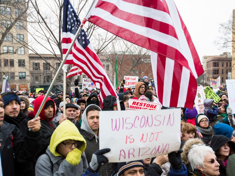 Thousands of Latino protesters and supporters carry signs outside the Capitol building to protest immigration bills on Feb. 18, 2016, Madison, Wis. The number of Latinos in Wisconsin has grown rapidly in recent years, now accounting for about 6.4 percent of the population.