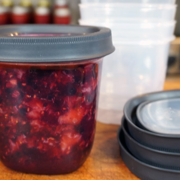 Triple Berry Freezer Jam in a plastic freezer safe container.