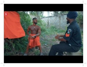 Broda Shaggi in red dress as herbalist and Officer Woos in black dress as Policeman