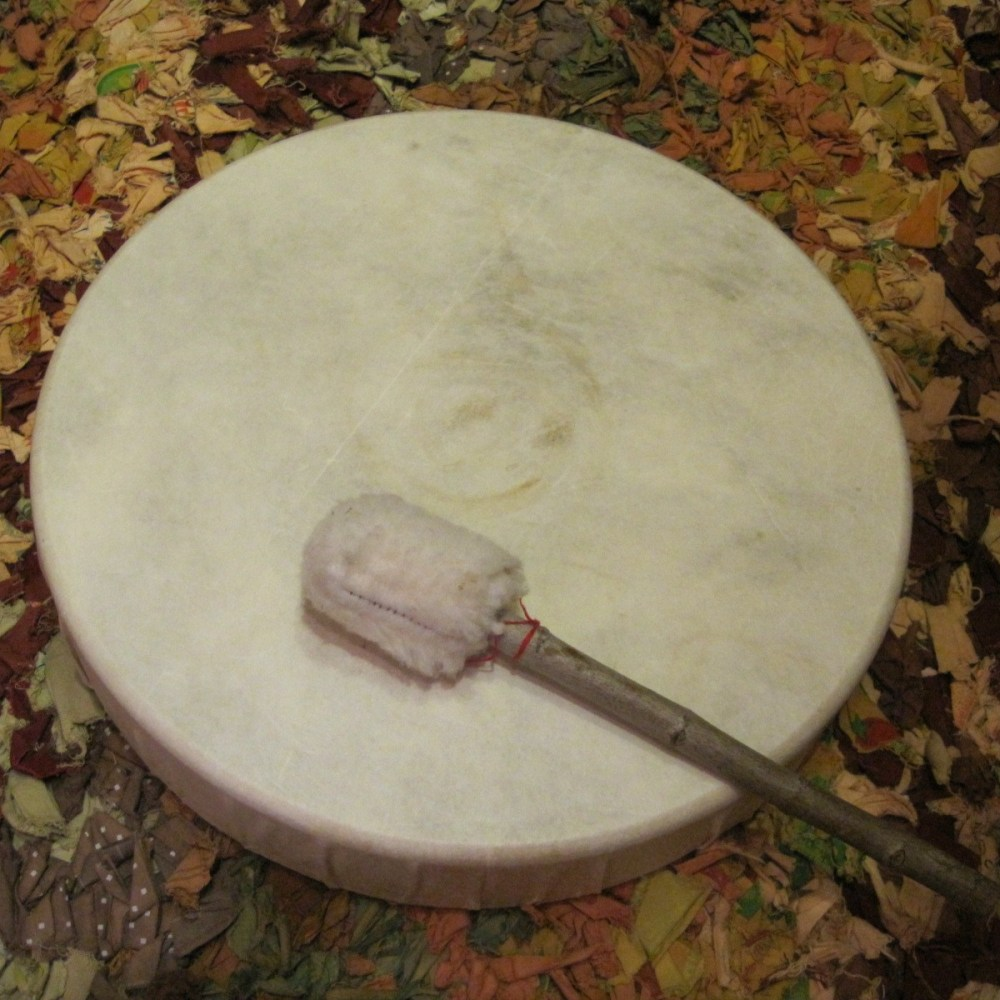 a hand-made frame drum with beater lying on it