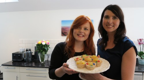 Lucy and YouTube baking guru Gemma Stafford holding up the cupcakes they made when filming for the RNIB