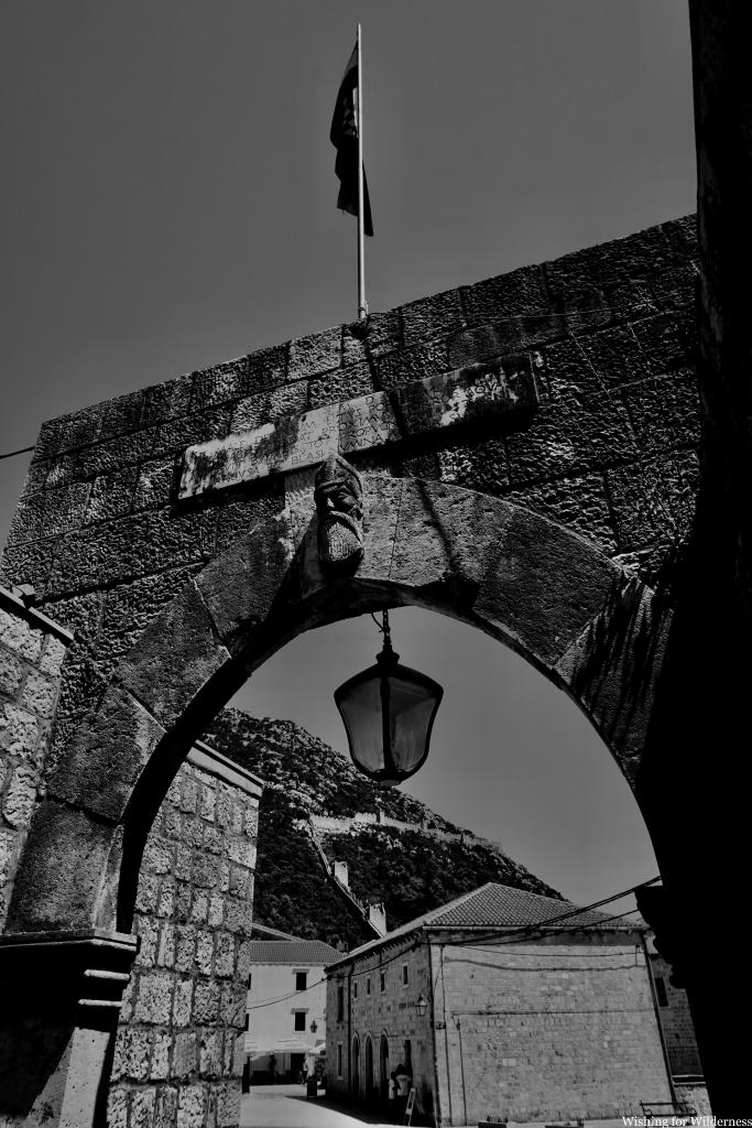 Black and white photo of ancient wall and arch