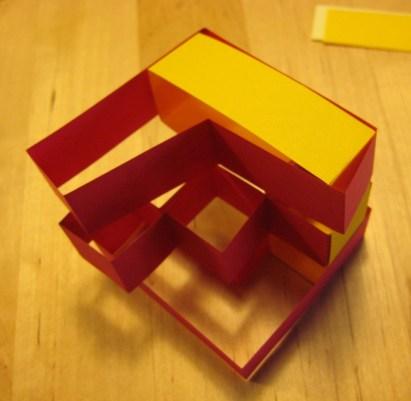F-blokje 6 in wording: drie rode stroken en een oranje zijn al klaar en door elkaar gevlochten.