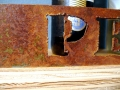 Close-up showing the freehand style of the cutout and rust