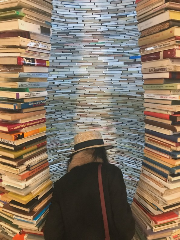 girl in front of tunnel of books in municpal library of prague