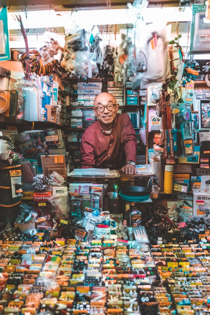 man smiling in battery electronics store front