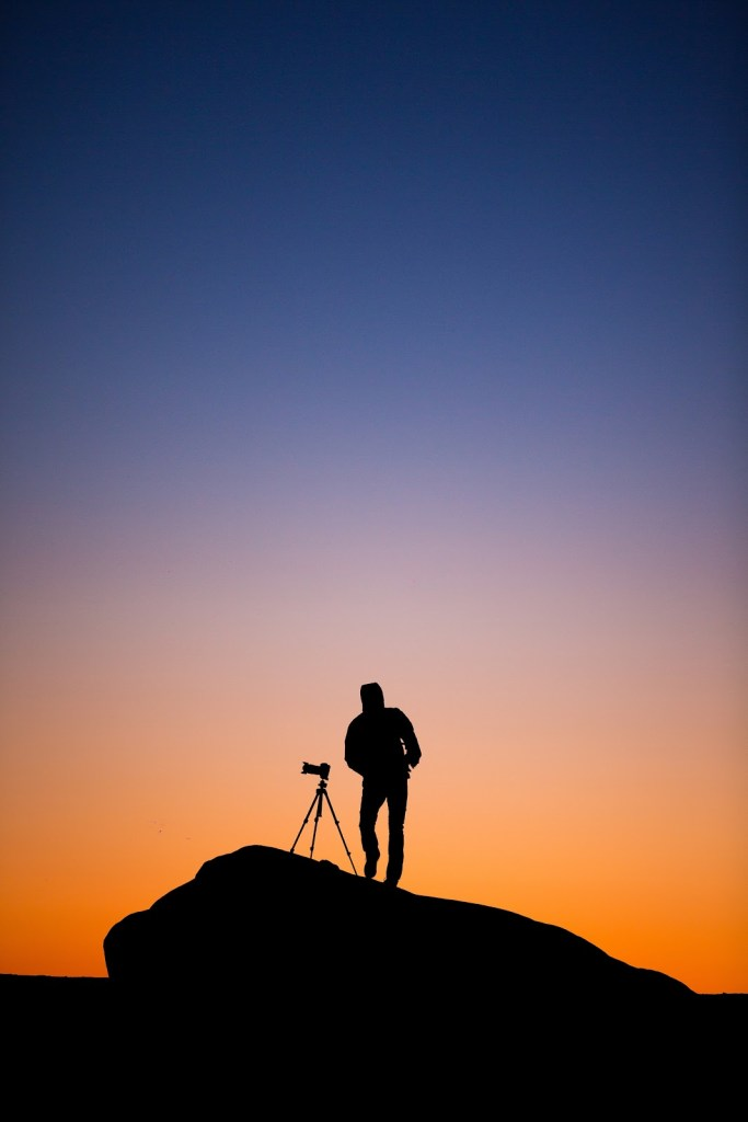 sillhouette of person at sunset taking a photo