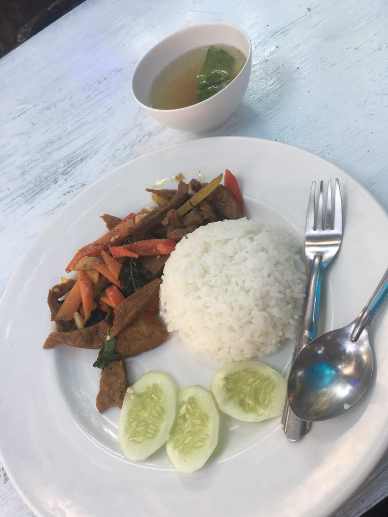 Photo of delicious vegetarian meal with rice, cucumbers, and a meat substitute stir-fried with vegetables at a cafe in Chiang Mai, Thailand