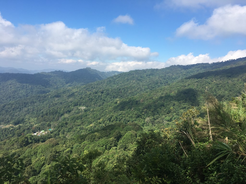 Beautiful viewpoint of lush green hills, rolling mountains and blue skies in Chiang Mai, Thailand.