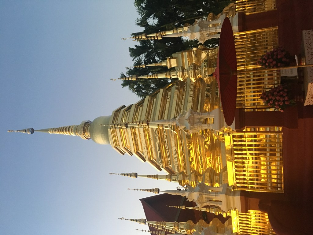 Photo of shining gold stupa at sunset Wat Phan Tao in Chiang Mai, Thailand