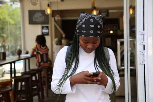 Photo of African-American woman texting on her phone by Angelo Moleele