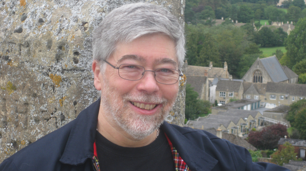 Wilkie standing on church roof with cotswold stone wall behind (part of parapet) and cotswold building visible behind below him