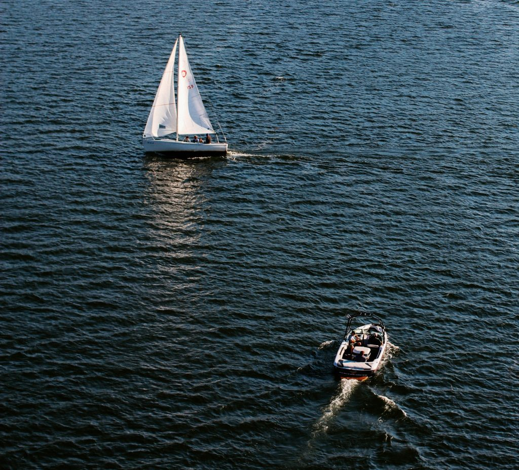 sailboat and powered dinghy on water