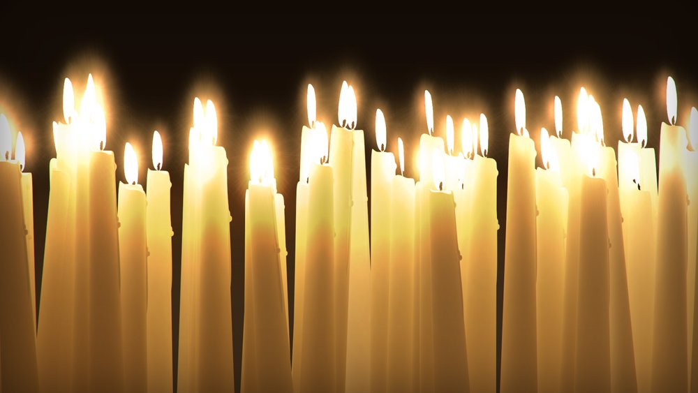 Many taper candles, lit